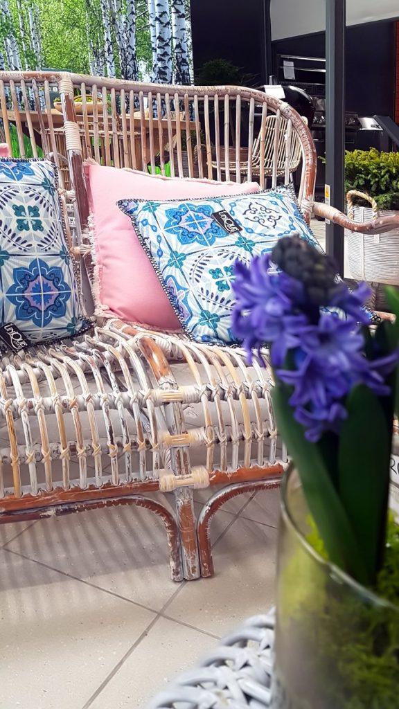 Targi Green Days, meble ogrodowe, meble z rattanu, Garden Space, sofa z rattanu z niebieskimi poduszkami, różowa poduszka, na pierwszym planie fioletowy hiacynt