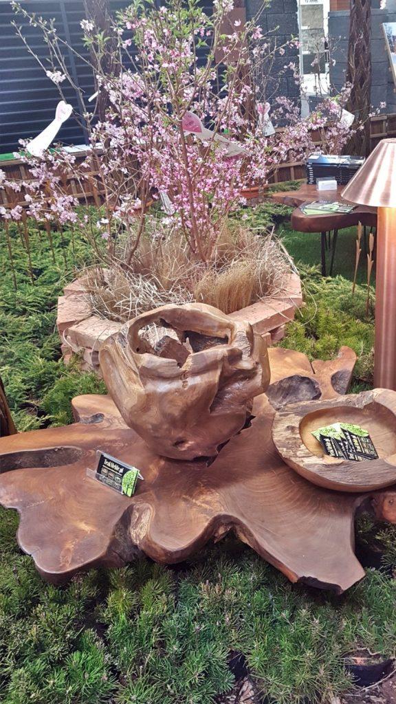 Targi Green Days, wystawa ogrodnicza, drewniane misy, zielona kosodrzewina, ogrodowa lampa z miedzi, w tle kwitnące drzewko