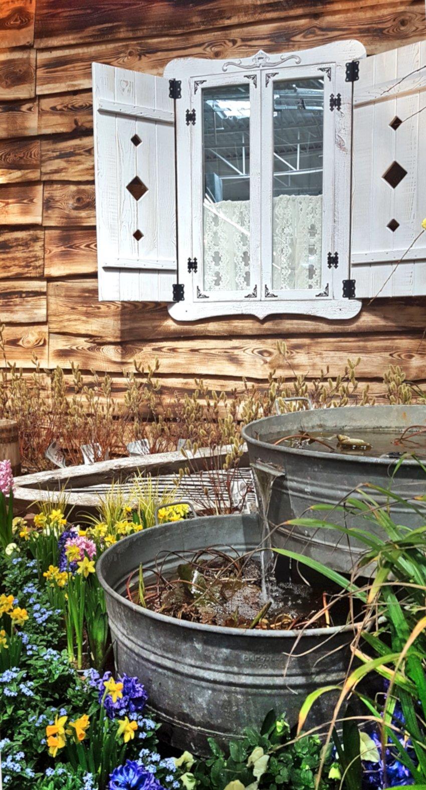 Targi Green Days, wystawa ogrodnicza, metalowe wanny, metalowa balia, źródełko ogrodowe, kolorowe kwiatki, żonkile, niezapominajki, w tle wiejska chata z białymi okiennicami
