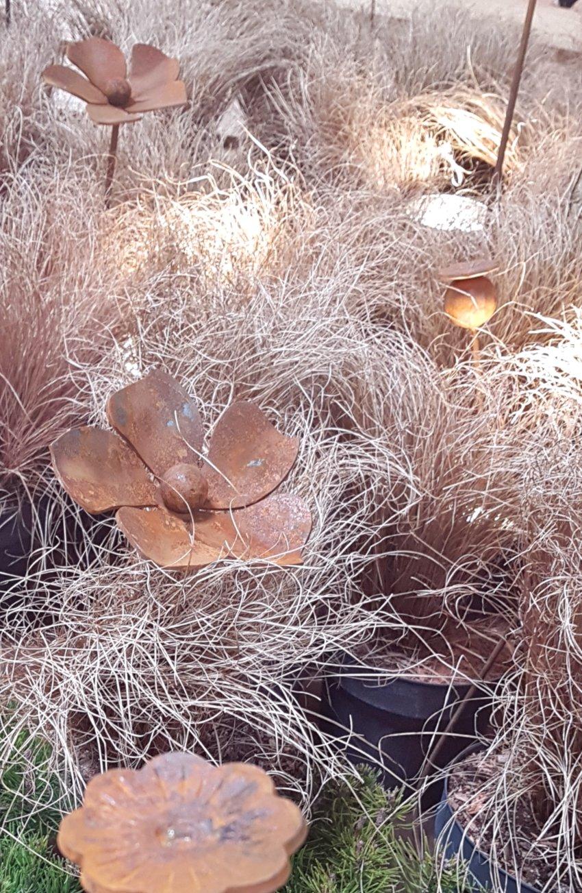 Targi Green Days, wystawa ogrodnicza, metalowe dekoracje do ogrodu, wykute rośliny kwiaty wbita w ziemie pomiędzy suchymi trawami