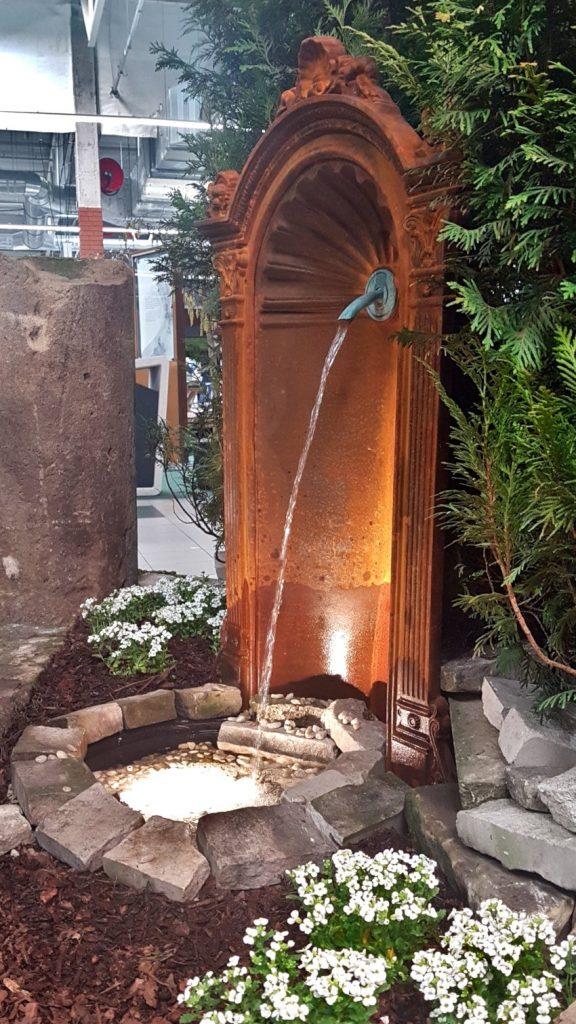 Targi Green Days, Architektura Ogrodowa, Chronos, fontanna z żeliwa, starodawna fontanna, stylizowane źródełko,w tle zielone drzewka żywotniki ogród