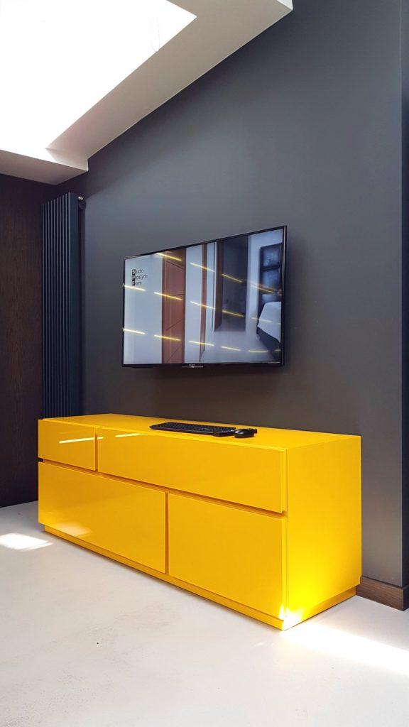 Ecomalta, Studio Prostych Form, żółta szafka RTV pod ścianą, na ścianie wisi telewizor, w rogu wysoki czarny grzejnik pionowy dekoracyjny, w tle szaara gładka ściana