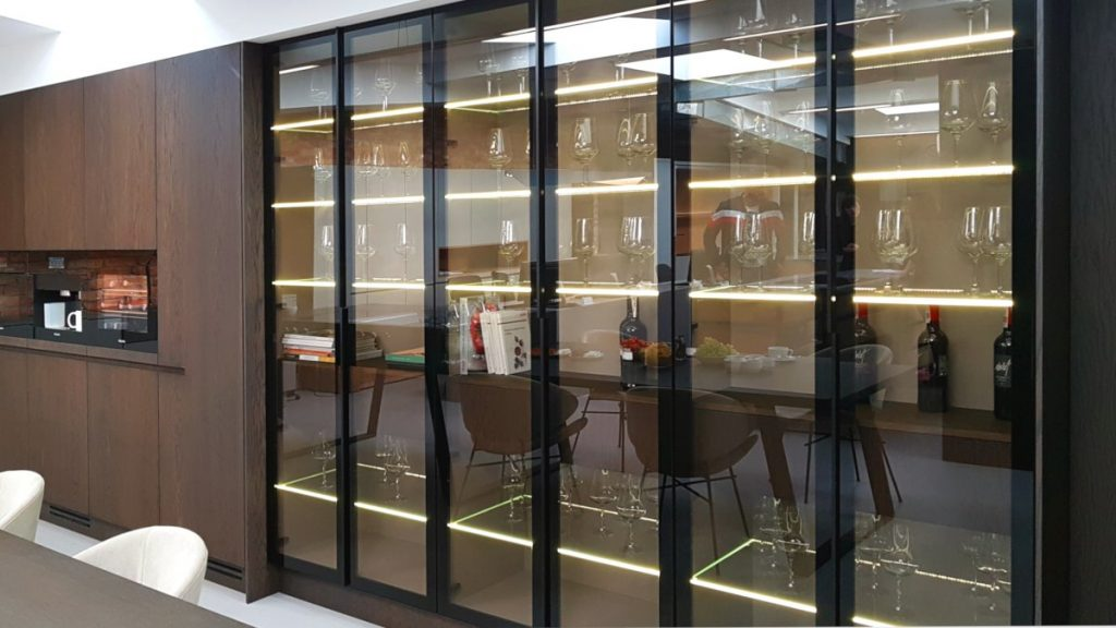 Ecomalta, Studio Prostych Form, meble kuchenne z zabudowanym ekspresem do kawy, zabudowa kuchenna w ciemnym brązie, obok przeszklona witryna w czarnej ramie