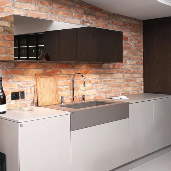 Ecomalta, Studio Prostych Form, meble kuchenne szare obłożone ecomaltą w kolorze szarym, górne szafki czarne w wysokim połysku, górne szafki jak czarne lustro, obok zabudowa kuchenna w ciemnym brązie, w tle ceglana ściana