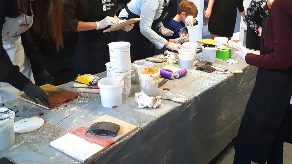 Ecomalta, okładzina, stół przygotowany do nakładania ecomalty, kilka opakowań pudełek wiaderek z kolorami ecomalty, deseczka z nałożoną ecomaltą, fioletowy wałek z odciskanym wzorem, wiele osób stoi przy stole i nakłada ecomalte na swoje deseczki, relacja z warsztatów ecomalty