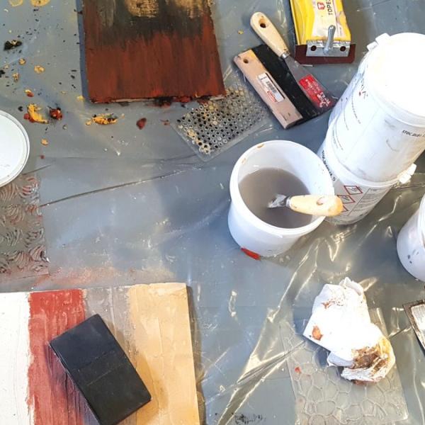 Ecomalta, okładzina, stół przygotowany do nakładania ecomalty, kilka opakowań pudełek wiaderek z kolorami ecomalty, deseczka z nałożoną ecomaltą, fioletowy wałek z odciskanym wzorem, relacja z warsztatów ecomalty