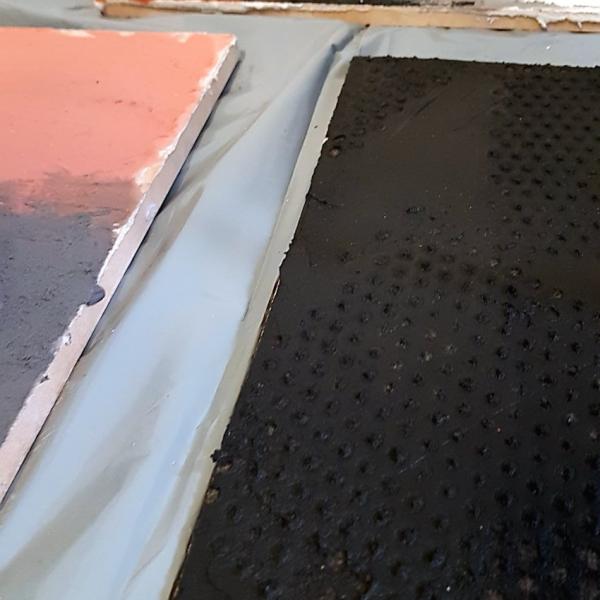 Ecomalta, co na podłogę, okładzina, panel z odpiśnientym wzorem w Ecomalcie, kolor czarny szary czerwony, panele leżą na podłodze pośród innych paneli