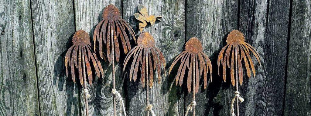 Targi Green Days, wystawa ogrodnicza, metalowe dekoracje do ogrodu, wykute rośliny jeżówki oparte o drewniany płot, w tle stare poszarzałe drewniane deski