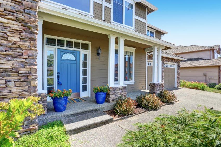 Kolorowe drzwi wejściowe, dom z niebieskimi drzwiami, na werandzie niebieskie donice z kwiatami, białe okiennice