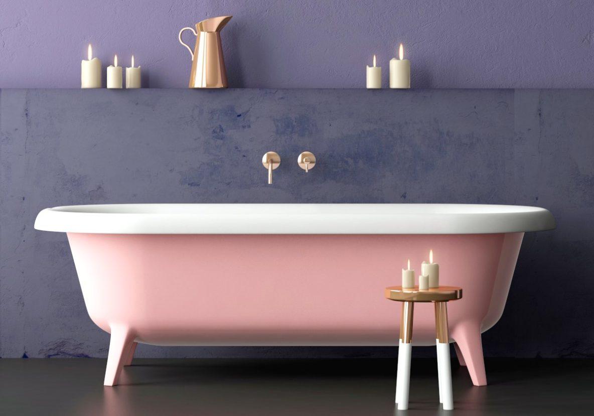 Wanna wolnostojąca, różowa wanna, na tle fioletowej kamiennej ściany, drewniany stołek ze świecami, złoty kran, złota bateria wannowa