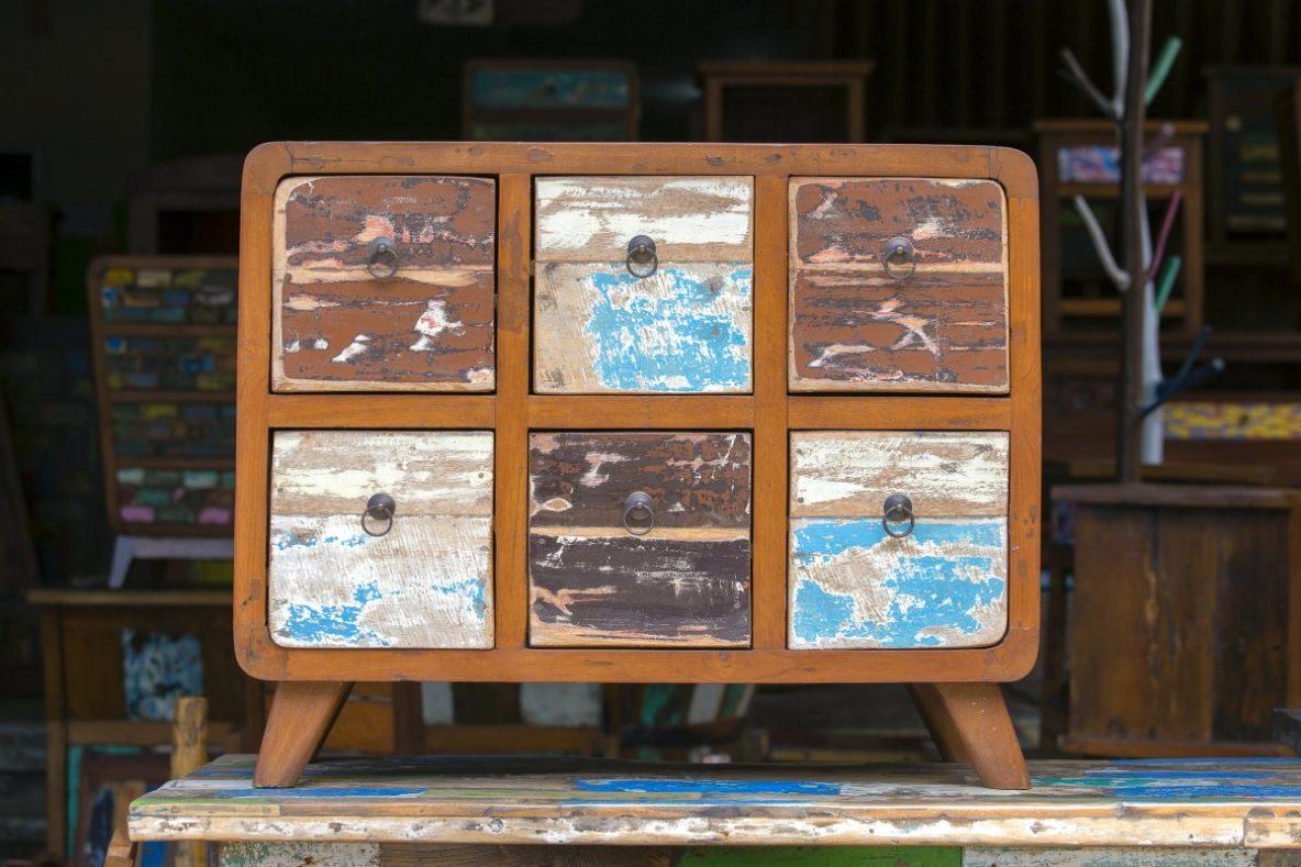 Malowanie Mebli, stara komoda w stylu vintage stoi w magazynie na stole, przetarte niebieskie szuflady
