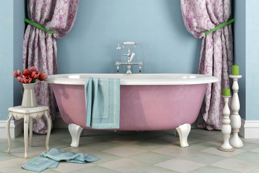 Wanna wolnostojąca, różowa wanna z białymi nóżkami na tle błękitnej ściany, obok wysokie świeczniki z zielonymi siecami, stolik pomocnik z wazonem, dekoracyjne zasłony w różowe wzory, stojąca podłogowa bateria typu telefon