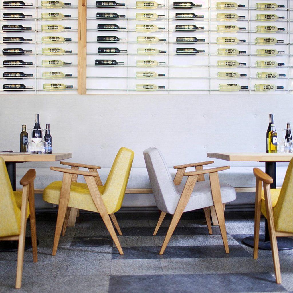 Meble PRL, łączenie starych mebli z nowymi, Styl PRL we wnętrzach, Jak połączyć antyki z nowoczesnym wnętrzem, fotel Chierowskiego 366 szary i zółty, fotele Chierowskiego stoi w pomieszczeniu typu kawiarnia, na ścianie ułożone są butelki z winem