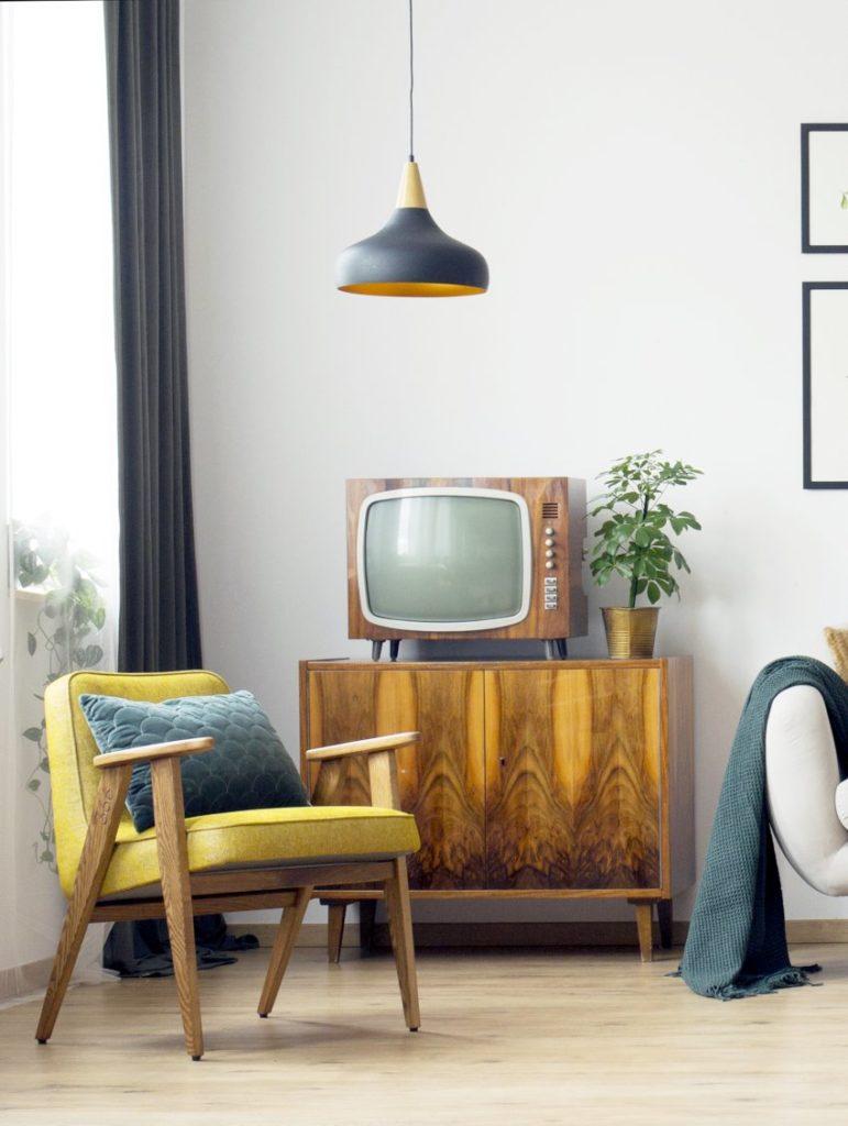 Meble PRL, łączenie starych mebli z nowymi, Styl PRL we wnętrzach, Jak połączyć antyki z nowoczesnym wnętrzem, komoda RTV na której stoi stary kineskopowy telewizor, obok stoi żółty fotel Chierowski 366, u góry wisi czarna lampa