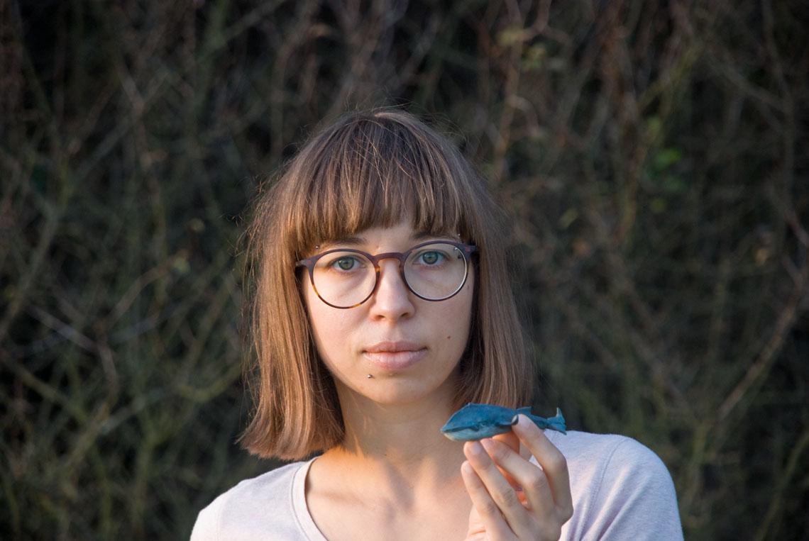 kobieta trzyma w dłoni małą rzeźbę wieloryba, artystka Joanna Krzepina