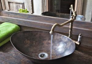 Styl rustykalny pomysł na łazienkę miedziana umywalka stoi na drewnianym blacie kran retro miedziany stojąca bateria umywalkowa retro leje się woda z kranu duże lustro w deranianej ramie w łazience w odbiciu drewniane drzwi