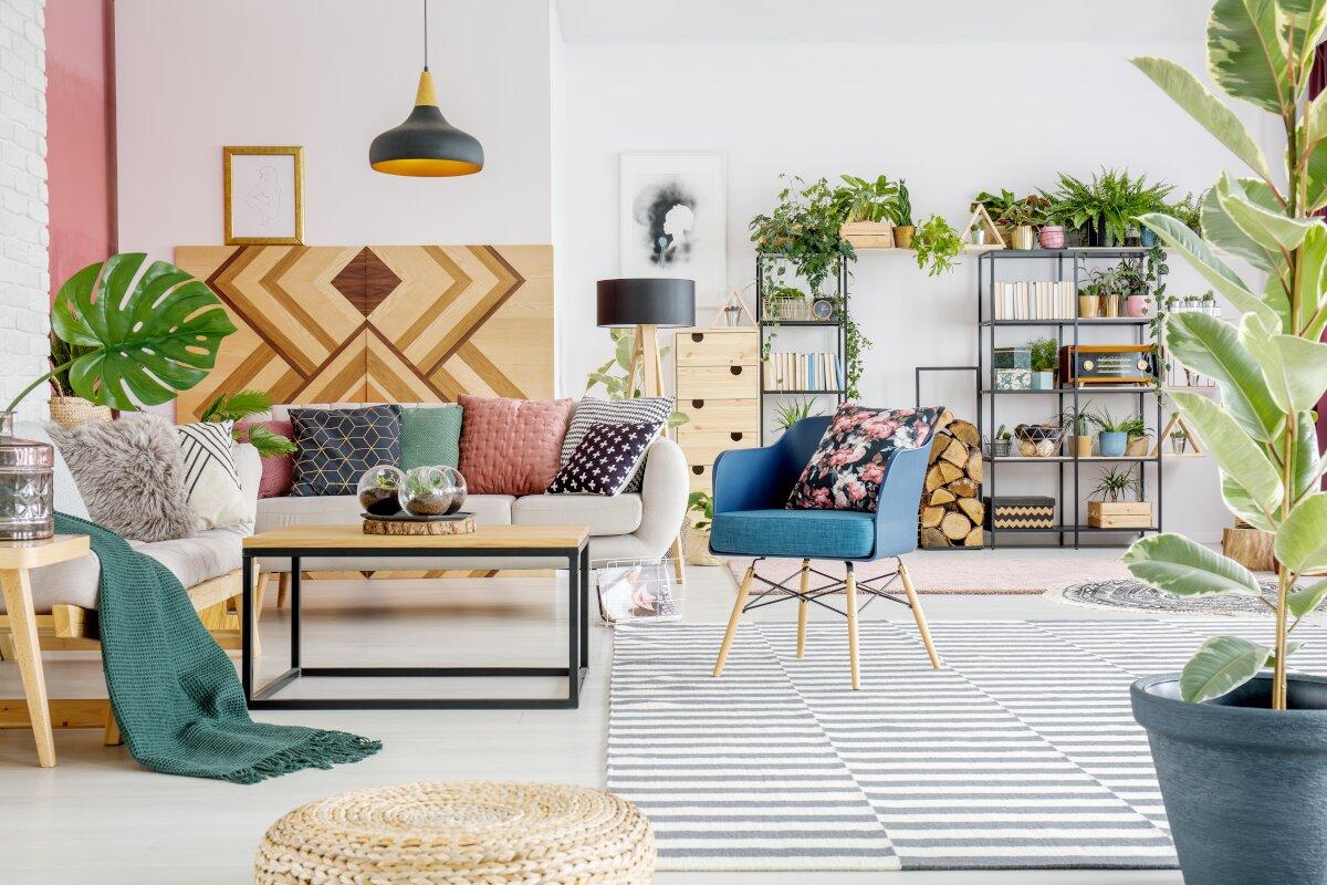 Dekoracje do salonu, pokój z białymi ścianami, w tle metalowe regały z książkami i dekoracjami, na przodzie biała kanapa i niebieski fotel, z tyłu kanapu drewniana dekoracji w geometryczne wzory,wokoło dużo roślin doniczkowych, rośliny w salonie