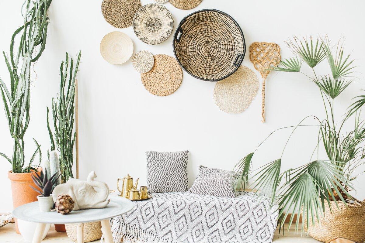 Dekoracje do salonu, na białej ścianie wiszą okrągłe plecionki z trawy morskiej, wikliny i sznurka, na drewnianej podłodzę stoją duże donice z roślinami, kaktusy w ceramicznych donicach, palma w wyklinowym koszyku