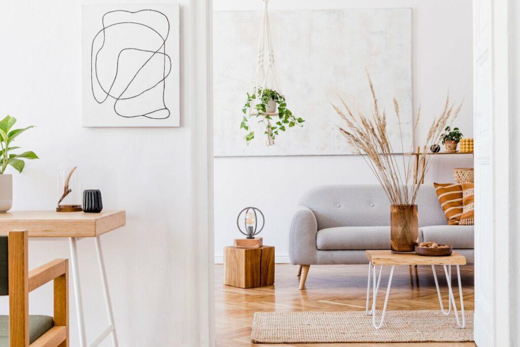 Projektowanie wnętrz cennik, widok na salon z białą ścianą na której jest duży jasny obraz, na drewnianym parkiecie stoi szara kanapa i stoliki z drewnianych pieńków, rośliny doniczkowe zwisają z kwietników uplecionych z makramy, kwietnik z makramy