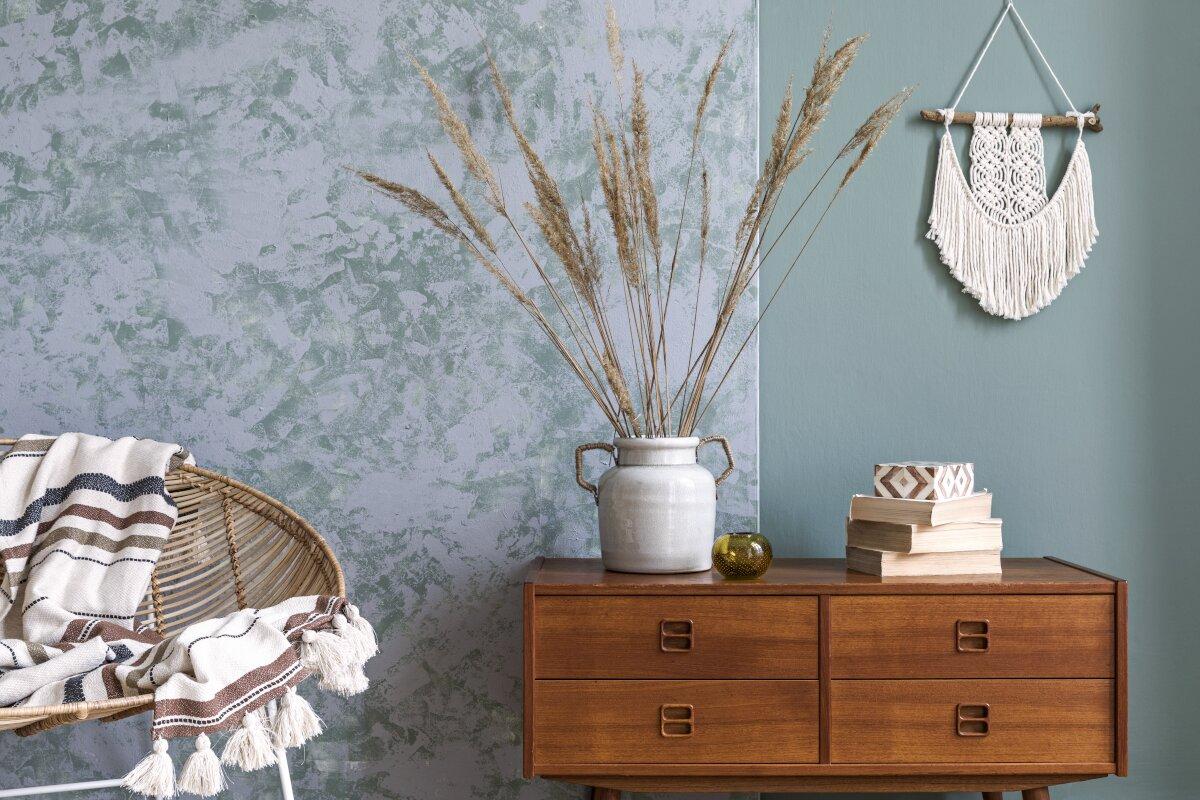Dekoracje do salonu, dekoracje stawiane na komodzie, na drewnianej komodzie stos książek, ceramiczny wazon ze złotymi uchwytami, w wazonie suche trawy, obok ratanowy fotel z kocem w pasy, w tle ściana stylizowana na starą, na ścianie wisi pleciona makrama, Katalogowe dekoracje