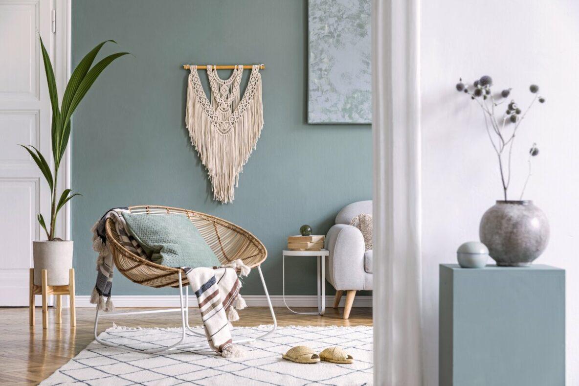 Dekoracje do salonu, plecionka z makramy na ścianie, makrama, niebieska ściana, nowoczesny fotel z rataniu, bujany fotel z wikliny, roślina doniczkowa w drewnianej podstawce, dreaniany stojak na kwiatki, dywan pleciony biały w frędzelkami, niebieski postument dla kwiatka