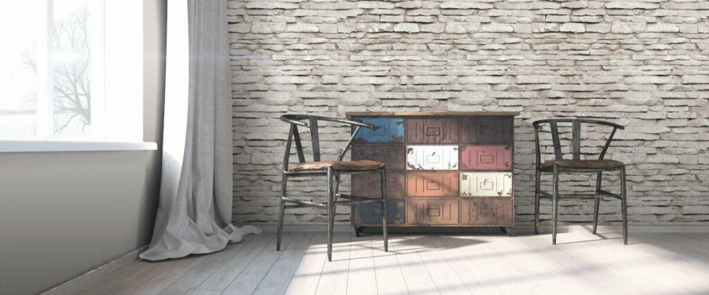 Nowoczesne wnętrze w stylu loft. Na tle ściany ze starej szarej cegły komoda z szufladami obok stoją dwa stare, drewniane krzesła
