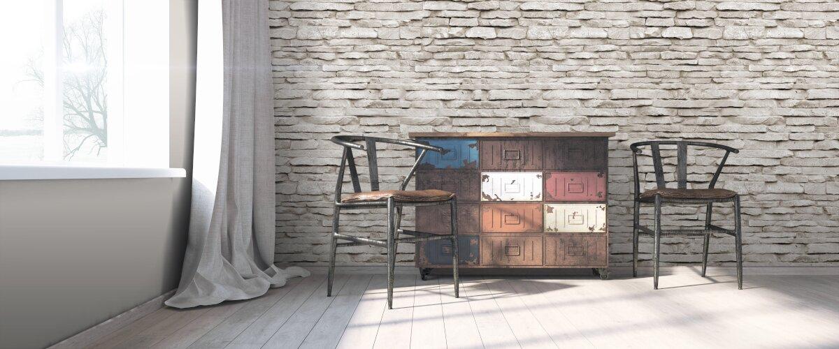 Jak nie urządzać mieszkania,Nowoczesne wnętrze w stylu loft. Na tle ściany ze starej szarej cegły komoda z szufladami obok stoją dwa stare, drewniane krzesła