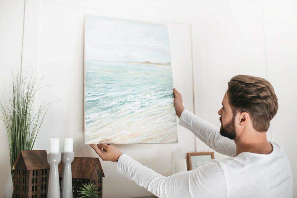 Młody mężczyzna wiesza na ścianie obraz z morzem. W tle biała ściana i dekoracje z drewnianych domków. Szklane świeczniki, Sztuczna roślina doniczkowa