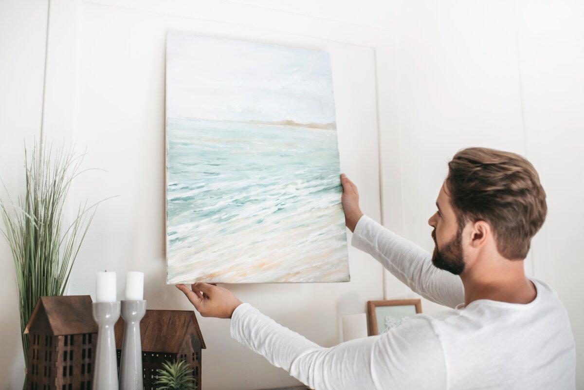 Jak nie urządzać mieszkania, Młody mężczyzna wiesza na ścianie obraz z morzem. W tle biała ściana i dekoracje z drewnianych domków. Szklane świeczniki, Sztuczna roślina doniczkowa