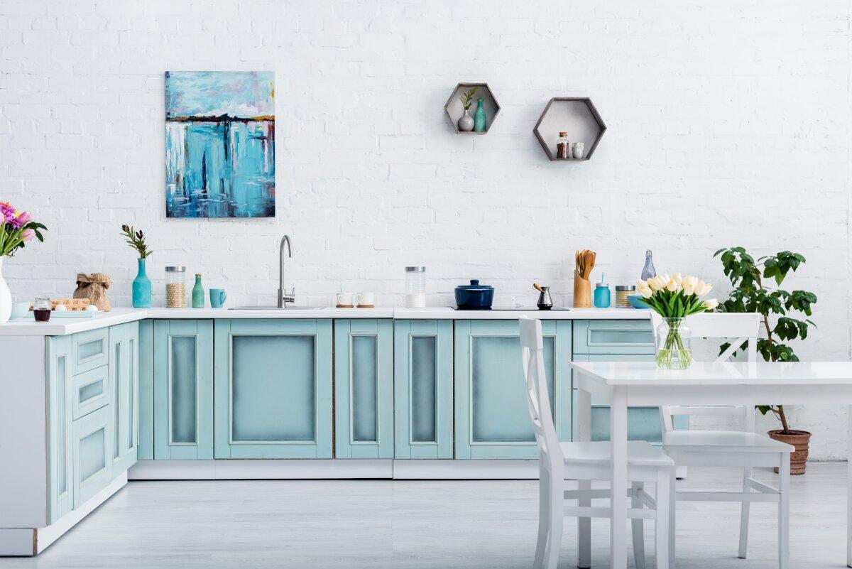 Dekoracje do salonu, duża biała ściana ze starą białą cegłą, rząd szafek kuchennych w kolorze niebieskim, szafki kuchenne pomalowane farbą kredową, szafki kuchenne pomalowane i cieniowane, kuchnia z białym blatem