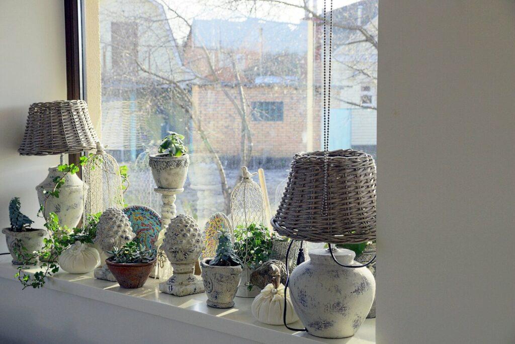 Na parapecie okiennym dużo dekoracji. Kwiaty doniczkowe w ceramicznych donicach. Lampy stołowe z wiklinowym abażurem