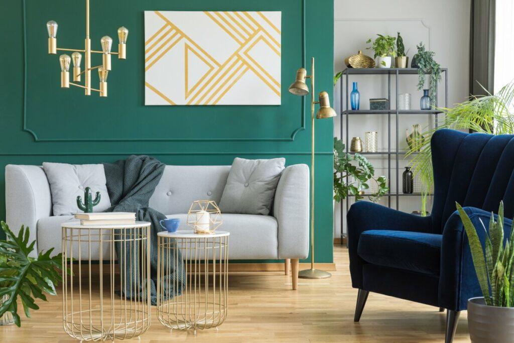 Dekoracje do salonu, salon z zieloną ścianą na której jest zielona sztukateria, salon ze sztukaterią, na tle zielonej ściany stoi szara kanapa, złote lampy wiszące i stojące, w tle metalowy regał z wazonami, na przodzie granatowy fotel i okrągłe złote ażurowe stoliki