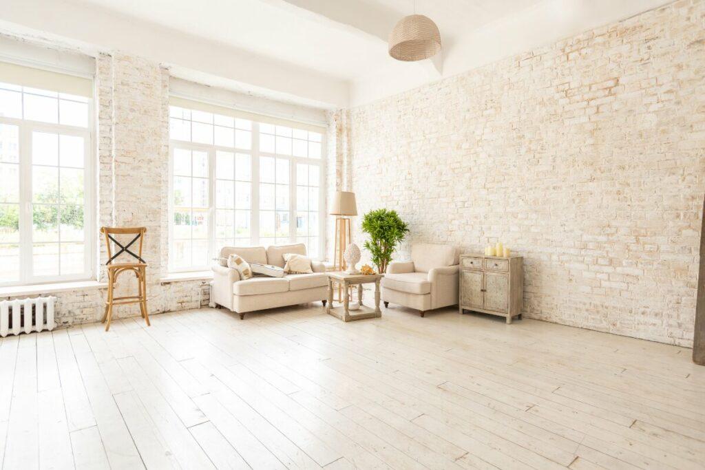 Duży salon, ściany ze starej cegły, w kącie klasyczna, kremowa sofa, fotel, komoda o stolik kawowy. Drewniana bielona podłoga, wiklinowa lampa, żyrandol z ratanu
