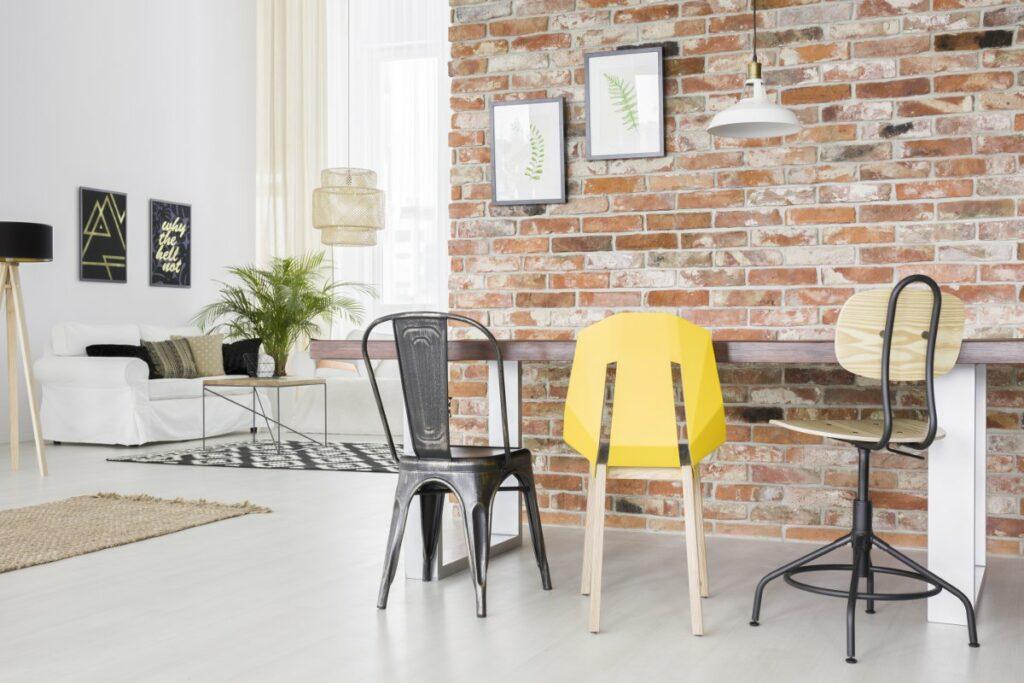 Jasne wnętrza, Salon z białymi ścianami, na jednej ścianie czerwona stara cegła, jasna podłoga biała kanapa wisząca lampa z wikliny, loftowe krzesła przy stole