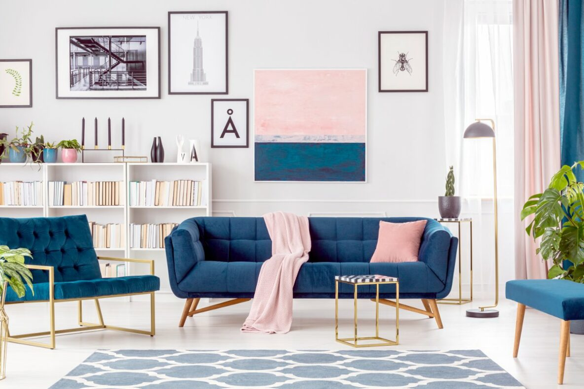 Jasne wnętrza, nowoczesny salon z białymi ścianami, niebieska kanapa pikowana kanapa, nowoczesne niebieskie fotele na złotych nogach, biały regał z książkami za kanapą na ścianie wisi obraz różowo niebieski, zasłony niebieskie i różowe złoty stoliki