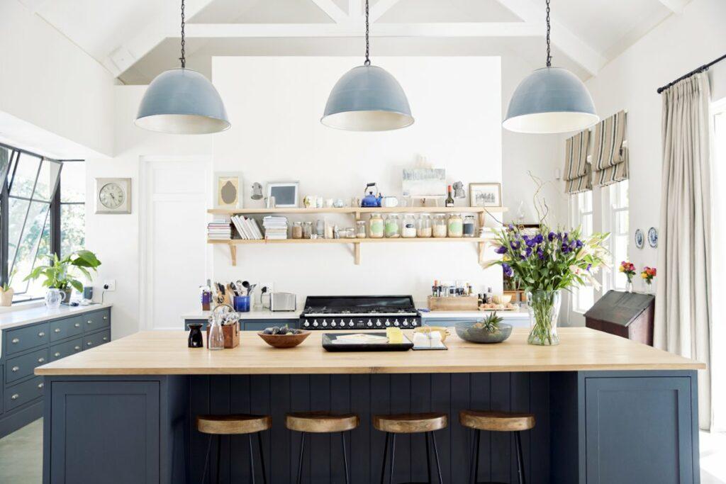 Jasne wnętrza, Jasna kuchnia z dużym oknem, niebieskie szafki kuchenne, Niebieska wyspa kuchenna, Białe ściany w kuchni, Półki kuchenne, kuchnia bez wiszących szafek, nad wyspa trzy wiszące niebieskie lampy, drewniane hok