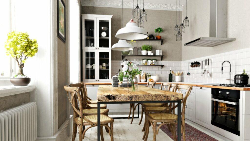 Jasne wnętrza, Kuchnia w stylu rustykalnym, tradycyjne białe szafki kuchenne, szara ściana, przeszklona tradycyjna kuchenna witryna, Drewniany stół na środku kuchni z grubym dębowym blatem, krzesła przy stole tradycyjne z plecionym siedziskiem