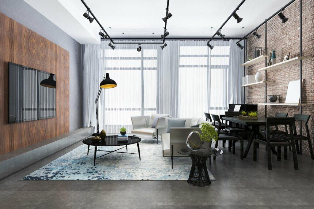 Pokój w nowoczesnym stylu, na środku biała sofa z fotelem i czarnym stolikiem kawowym, po prawej czarny stół jadalniany i ceglana ściana z metalową konstrukcją i drewnianymi półkami, po lewej wiszący na scianie telewizor sciana obłozona płyta meblową