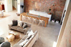 Jasne wnętrza, Widok z góry na salon szara podłoga dwie duże kanapy szare kanapy, plecione ze sznurka pufy, duży drewniany stół, biała duza komoda na tle ściany z czerwonej cegły