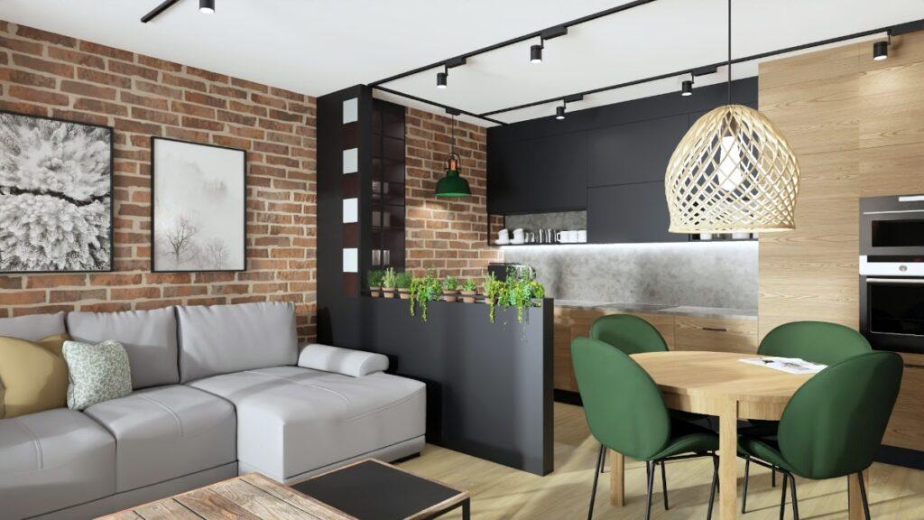 Małe mieszkanie projekt, kawalerka, drewno w połaczeniu z grafitem, kuchnia oddzielona od salonu murkiem, cegła na scianie, szara sofa, sofa IWC, plakaty na scianie, loftowa zielona lampa nad blatem kuchennym, okrągły stól, wiklinowa lampa nad stołem, zielone tapicerowane krzesła przy stole