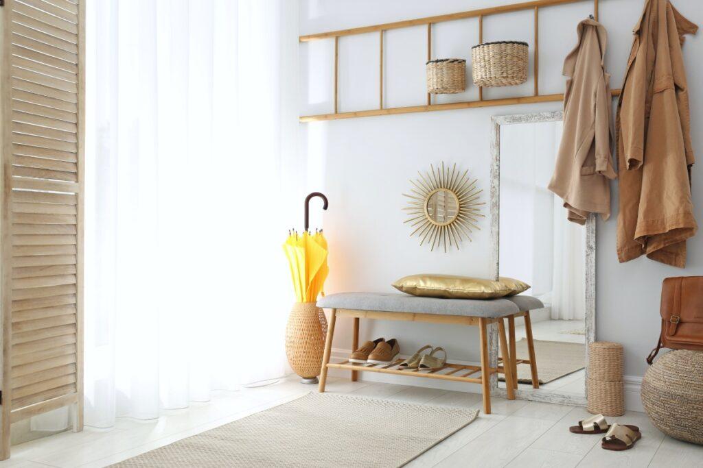Projekt przedpokoju, chodniki dywanowe do przedpokoju, mały przedpokój z siedziskiem, ławka z tapicerowanym siedziskiem, za ławką lustro w drewnianej ramie, nad ławką wieszak zrobiony w drewnianej drabiny, na podłodze chodnik dywanowy