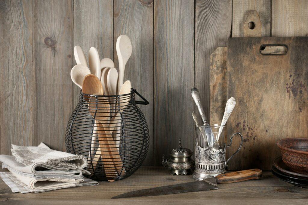 Kuchnia w stylu rustykalnym, akcesoria kuchenne w stylu vintage, srebrna szklanka ze sztućcami, druciany kosz z drewnianymi łyżkami, ceramiczne naczynia, ręczniki i deski do krojenia na drewnianym tle.
