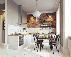 Kuchnia w stylu rustykalnym, na środku pomieszczenia stary prostokątny stół na cienkich nogach, krzesła z ratanowym siedziskiem, podłoga z bielonych desek, po lewej ciąg białych szafek kuchennych z drewnianym blatem, tle ściana z czerwonej cegły