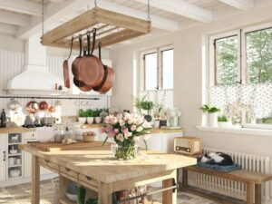 Kuchnia w stylu rustykalnym, na środku pomieszczenia drewniana wyspa, nad nią wiszą patelnie zaczepione na wieszakach, na suficie bielone belki, pod oknem ławka na której śpi kot, w tle biały wiejski okap i ściana z białych desek