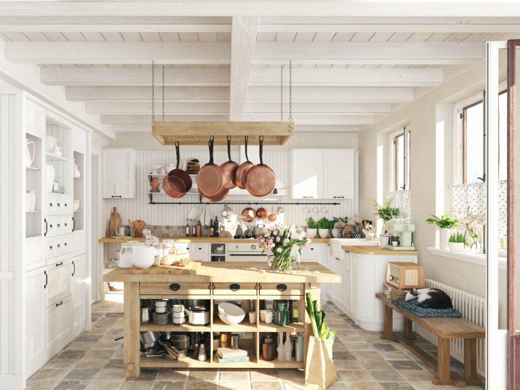 Kuchnia w stylu rustykalnym, na środku pomieszczenia drewniana wyspa pomocnik, nad nią wiszą patelnie po prawej pod oknem drewniana ławka na której śpi kot, po lewej biały rustykalny kredens w tle szafki kuchenne na ścianę z białych desek