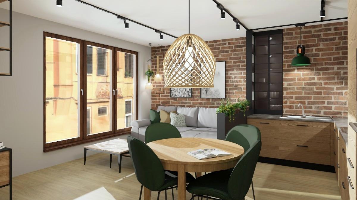 Jak urządzić kawalerkę, cagła na ścianie zielone krzesła, okrągły stół, wiklinowa lampa, szara kanapa