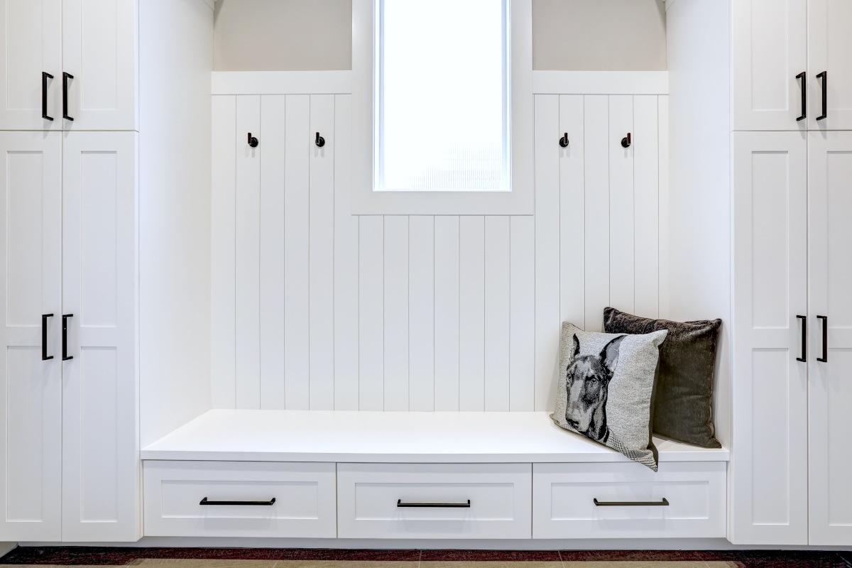 Siedzisko do przedpokoju, zabudowa meblowa w przedpokoju biała z czarnymi uchwytami, siedzisko białe pod siedziskiem trzy szuflady, po bokach siedziska dwie szafy na ubrania