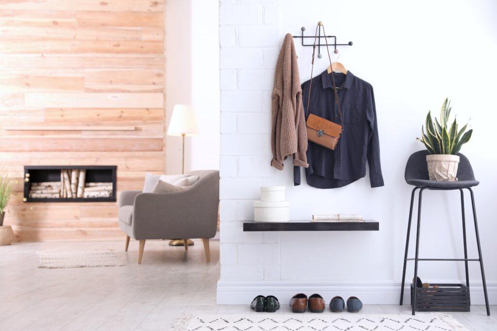 Projekt przedpokoju, wieszak do przedpokoju, metalowy wieszak na ubrania w przedpokoju na ścianie z białej cegły, w tle kominek w obudowie z drewna